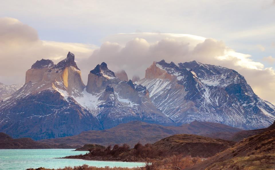 Cordillera con nubes y nieve a los pies una laguana
