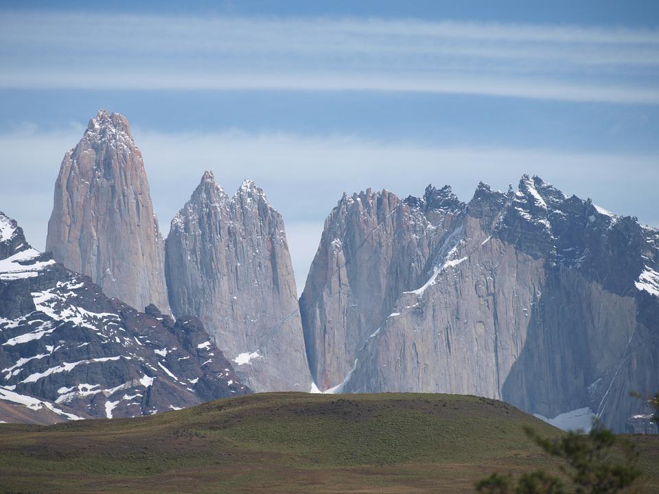 picos de montañas con nieve y a los pies prados verdes